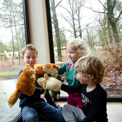 A group of children play with animal puppets