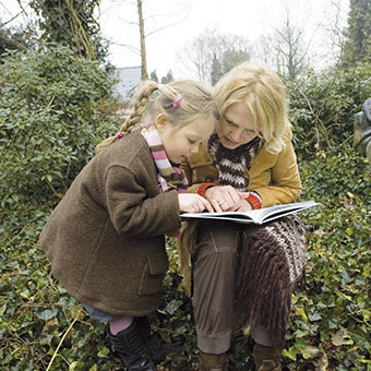 Woman and young girl reading a book together